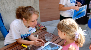 College-age COSIA student talking with a young student at a COSIA ocean festival